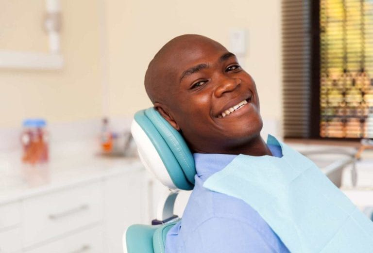 smiling patient undergoes dental checkup