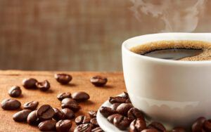 Cup of steaming coffee with beans